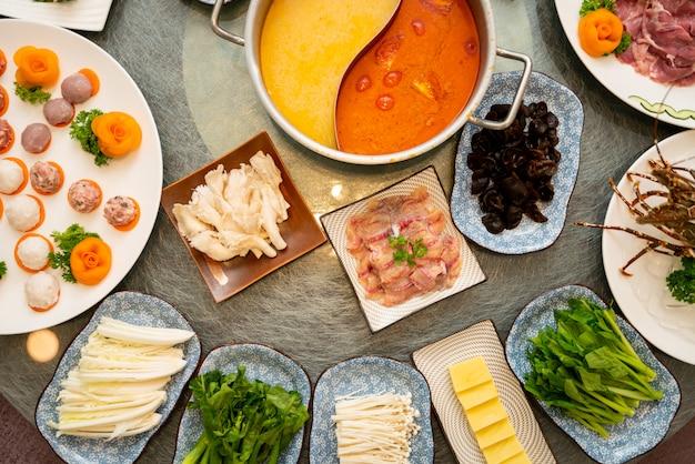 Foto de alto ângulo de sopa perto de um prato com carne crua com acompanhamentos