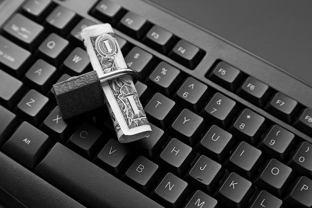 Foto de alto ângulo de um cadeado em torno de uma nota de um dólar em um laptop preto