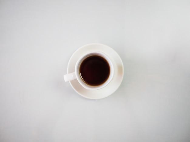 Foto de alto ângulo de um chá quente em uma xícara branca colocada em um prato branco