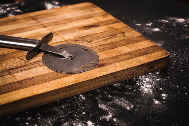 Foto de alto ângulo de um cortador de pizza em uma placa de corte de madeira em uma superfície preta