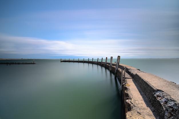 Foto de alto ângulo de um deck de madeira levando ao mar sob um céu azul claro