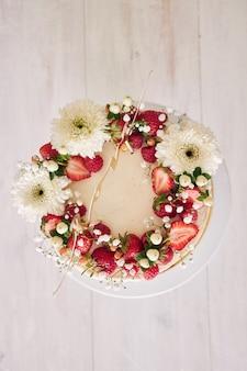 Foto de alto ângulo de um delicioso bolo de casamento branco com frutas vermelhas e flores na mesa de madeira branca