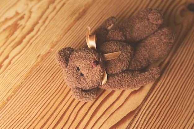 Foto de alto ângulo de um fofo urso de pelúcia em uma superfície de madeira