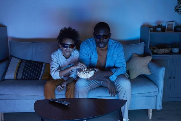 Foto de alto ângulo de um homem afro-americano e seu filho adolescente sentado no sofá da sala assistindo a um filme em 3d e comendo pipoca à noite