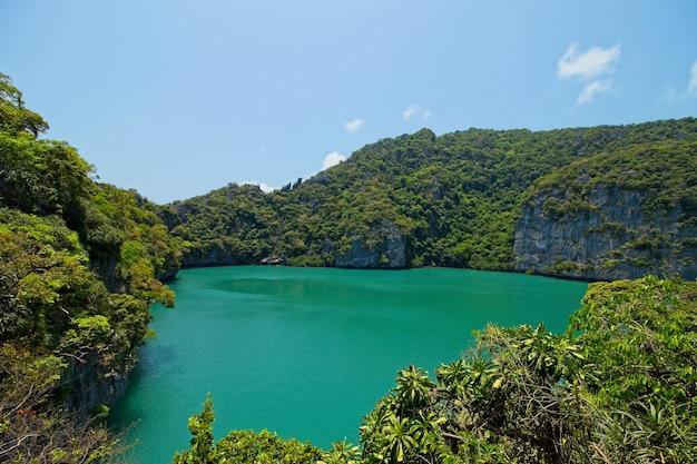 Foto de alto ângulo de um lago cercado por montanhas cobertas de árvores, capturada na tailândia
