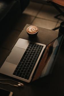 Foto de alto ângulo de um laptop com um cappuccino lindamente feito com arte de flores ao lado