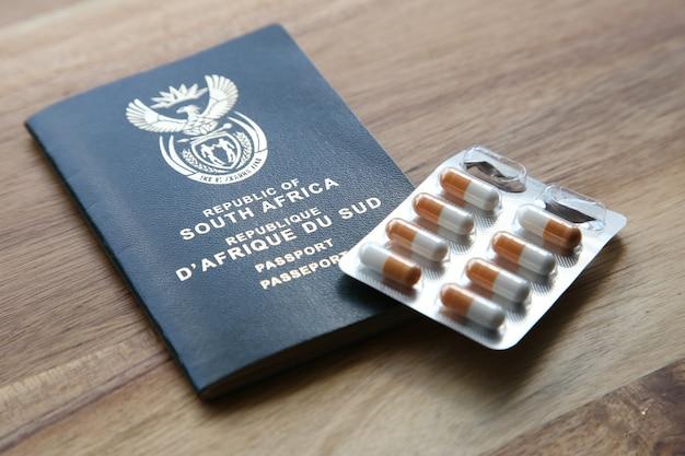 Foto de alto ângulo de um pacote de cápsulas e um passaporte em uma superfície de madeira