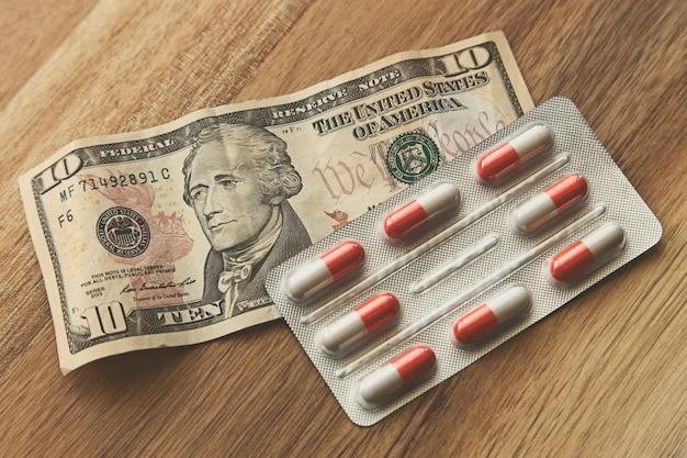 Foto de alto ângulo de um pacote de cápsulas em uma nota de um dólar em uma superfície de madeira