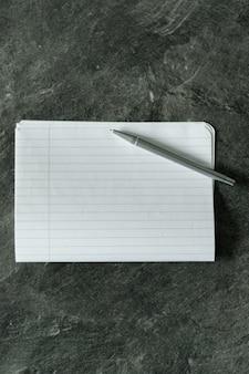 Foto de alto ângulo de um pedaço de papel branco com linhas e uma caneta de metal em uma superfície cinza