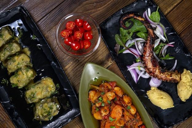 Foto de alto ângulo de um polvo grelhado e batatas com diferentes vegetais