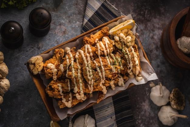 Foto de alto ângulo de um prato de frango frito delicioso e um pouco de alho em uma mesa