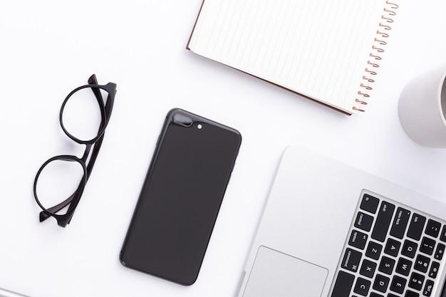 Foto de alto ângulo de um smartphone, laptop, óculos e um notebook em uma superfície branca