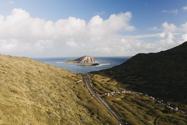 Foto de alto ângulo de um vale de montanha com uma pequena ilha em mar aberto