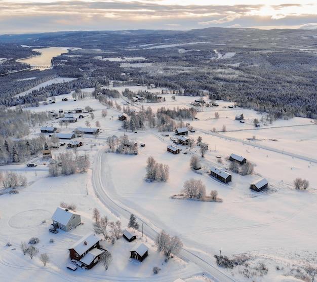 Foto de alto ângulo de uma cidade coberta de neve, rodeada por florestas e um lago sob um céu nublado