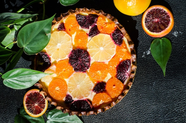 Foto de alto ângulo de uma deliciosa torta de laranja recém-assada em uma superfície preta