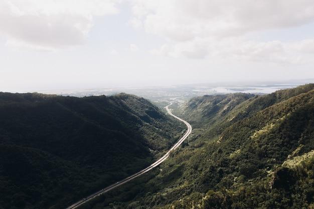 Foto de alto ângulo de uma estrada de vale com céu azul nublado
