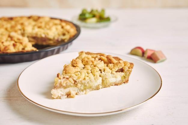 Foto de alto ângulo de uma fatia de torta de bolo rhabarbar crocante com alguns ingredientes em uma mesa