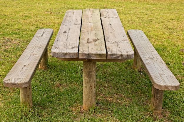 Foto de alto ângulo de uma mesa de madeira e bancos no campo coberto de grama