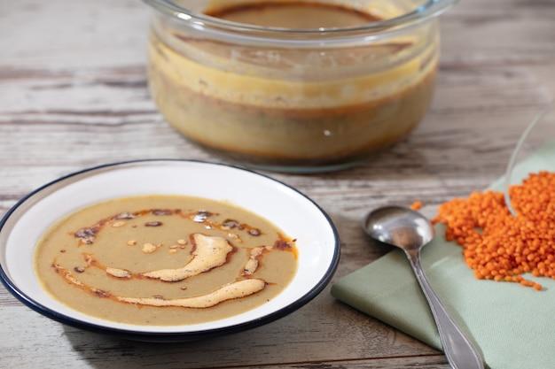 Foto de alto ângulo de uma panela, uma tigela de sopa e uma colher em uma superfície de madeira