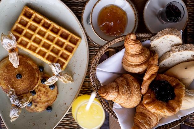 Foto de alto ângulo de uma panqueca e waffle em um prato redondo perto da bandeja com croissant