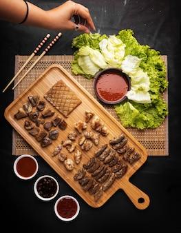 Foto de alto ângulo de uma pessoa agarrando alface por um prato de carne frita com batatas