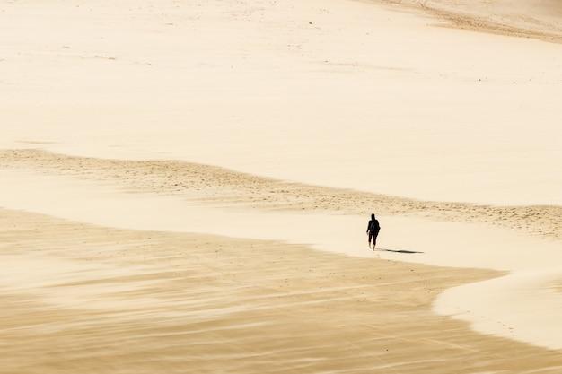 Foto de alto ângulo de uma pessoa andando descalço nas areias quentes do deserto