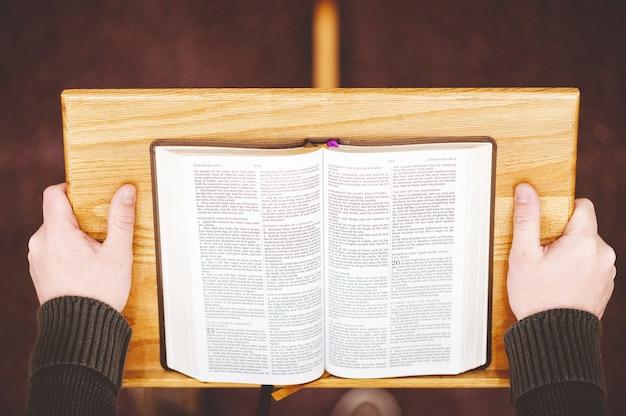Foto de alto ângulo de uma pessoa pregando a bíblia sagrada na tribuna do altar da igreja