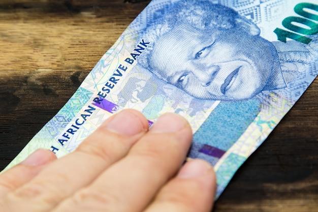 Foto de alto ângulo de uma pessoa segurando dinheiro sobre uma superfície de madeira