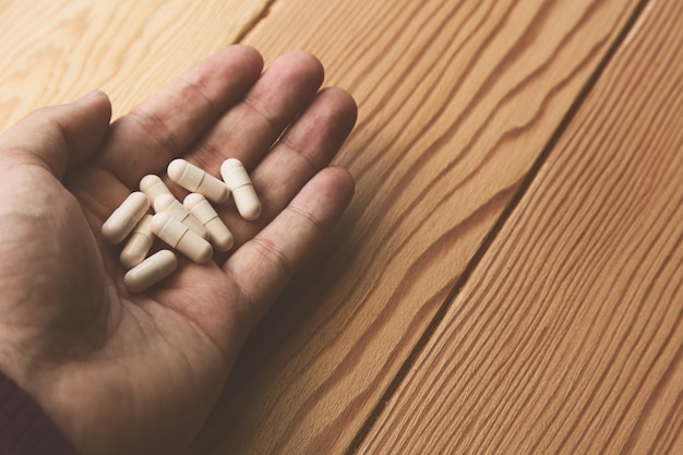 Foto de alto ângulo de uma pessoa segurando um monte de cápsulas brancas sobre uma superfície de madeira