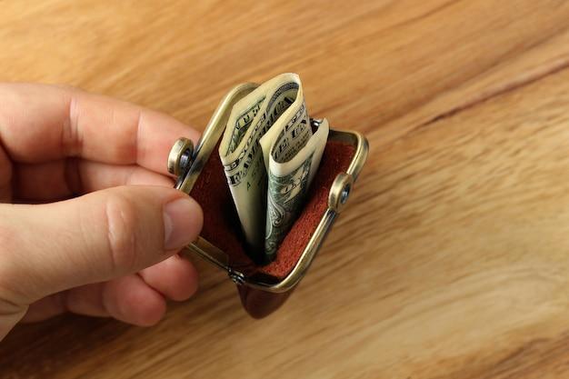 Foto de alto ângulo de uma pessoa segurando uma bolsa de moedas com algum dinheiro dentro sobre uma superfície de madeira