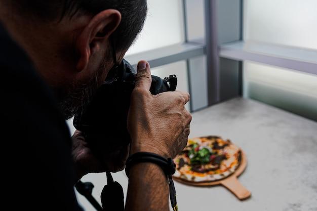 Foto de alto ângulo de uma pessoa tirando a foto de uma pizza na mesa