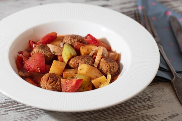 Foto de alto ângulo de uma tigela branca de sopa de carne e vegetais em uma mesa de madeira