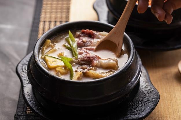 Foto de alto ângulo de uma tigela de sopa de vegetais deliciosa em uma mesa de madeira