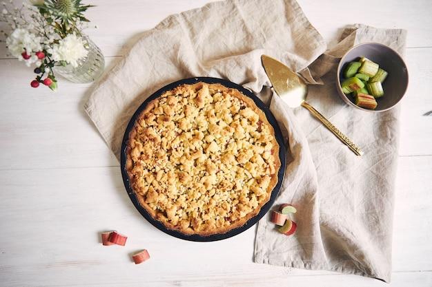 Foto de alto ângulo de uma torta de bolo rhabarbar crocante e alguns ingredientes em uma mesa branca