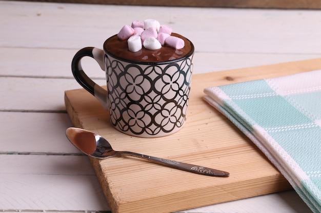 Foto de alto ângulo de uma xícara de chocolate quente com marshmallows em uma superfície de madeira