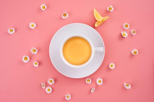 Foto de alto ângulo de uma xícara de suco de laranja cercada por pequenas flores de margarida em uma superfície rosa