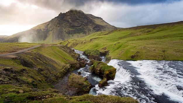 Foto de alto ângulo do rio passando pelos campos com o pico da montanha