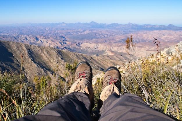 Foto de alto ângulo dos pés de uma pessoa sentada no topo de uma colina em um belo vale