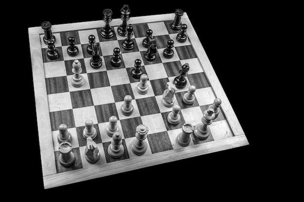 Foto de alto ângulo em tons de cinza de um jogo de tabuleiro de xadrez com as peças no tabuleiro