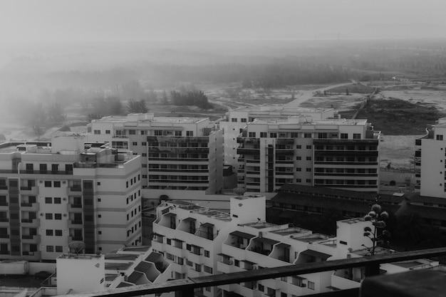 Foto de alto ângulo em tons de cinza dos edifícios na praia, capturada no pôr do sol com neblina