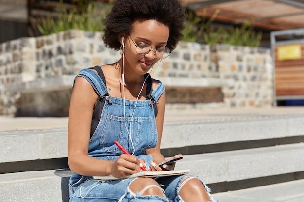 Foto de aluna ouve livro de áudio com fones de ouvido e telefone celular, escreve alguns registros e detalhes no diário, posa em escadas ao ar livre, se prepara para seminário, usa internet e tecnologia.