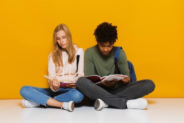 Foto de alunos entediados ou chateados de 16 a 18 anos lendo livros enquanto estão sentados no chão com as pernas cruzadas, isolada sobre um fundo amarelo