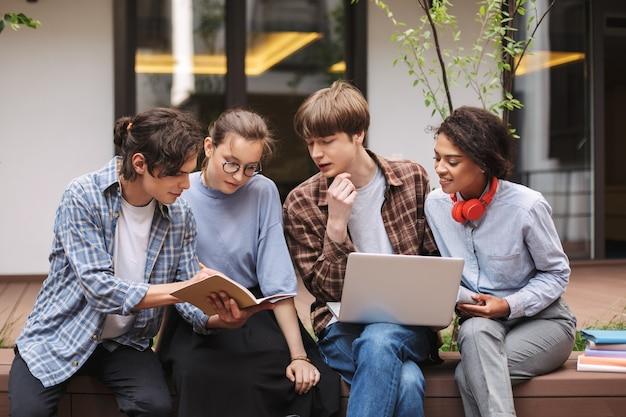 Foto de alunos sentados no banco com um laptop e um livro enquanto passam um tempo no pátio da universidade