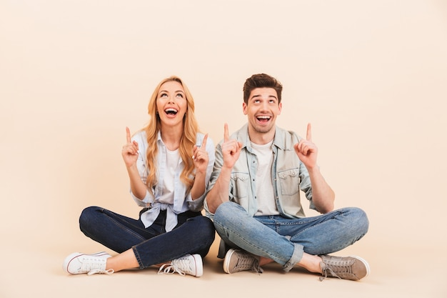 Foto de amigos animados, homem e mulher de 20 anos, em roupas jeans, sentados no chão com as pernas cruzadas e apontando os dedos para cima na copyspace, isolado sobre uma parede bege