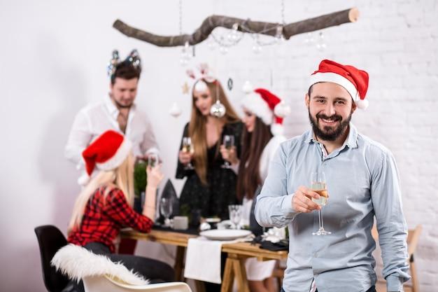 Foto de amigos felizes curtindo as férias com foco no homem em primeiro plano com um chapéu vermelho de natal
