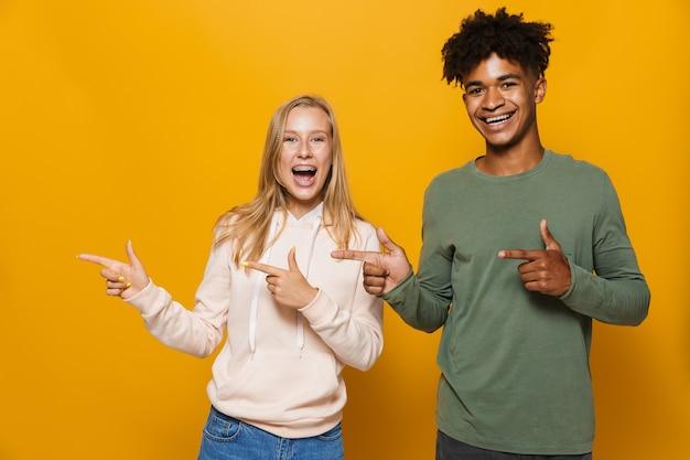 Foto de amigos felizes, homem e mulher de 16 a 18 anos, com aparelho dentário, rindo e apontando o dedo para o lado na copyspace, isolada sobre fundo amarelo