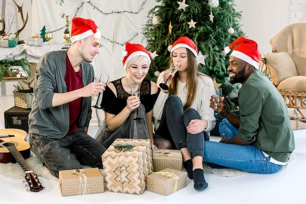 Foto de amigos rindo comemorando ano novo com champanhe em quarto aconchegante e decorado