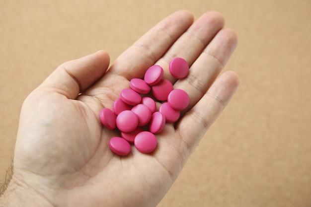 Foto de ângulo alto da mão de um humano com um punhado de pílulas rosa
