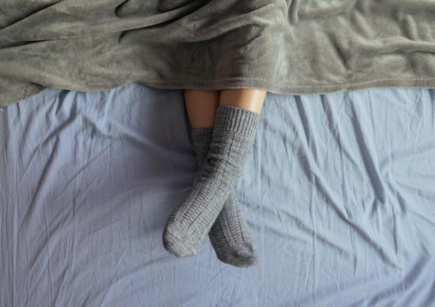 Foto de ângulo alto das pernas de uma mulher em meias de tricô cinza sob o cobertor