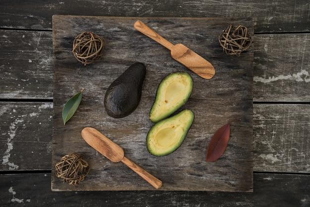 Foto de ângulo alto de abacates cortados e colheres de madeira em uma superfície de madeira